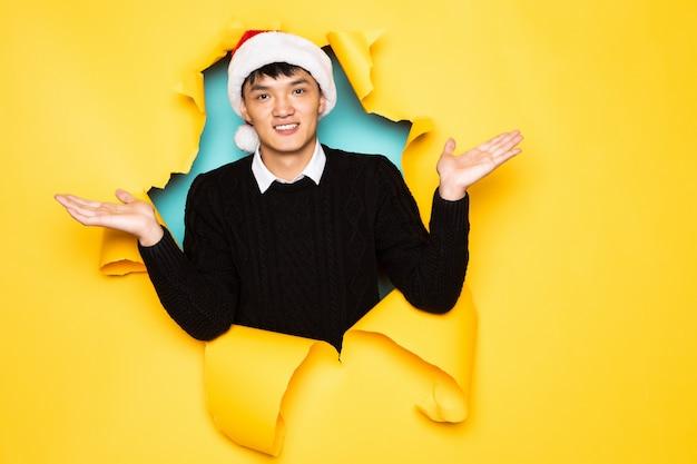 O jovem chinês com chapéu de papai noel e mãos levantadas mantém a cabeça no buraco da parede amarela rasgada. cabeça masculina em papel rasgado. Foto gratuita