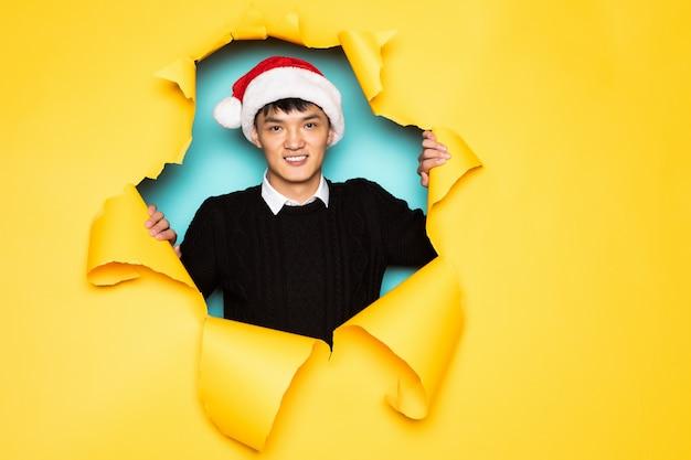 O jovem chinês com chapéu de papai noel mantém a cabeça no buraco da parede amarela rasgada. cabeça masculina em papel rasgado. Foto gratuita