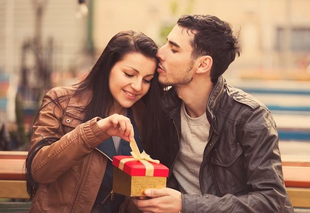 O jovem dá um presente para uma jovem no café e eles estão se beijando. Foto Premium