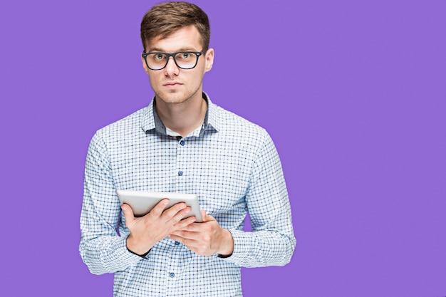 O jovem de camisa trabalhando no laptop em lilás wal Foto gratuita