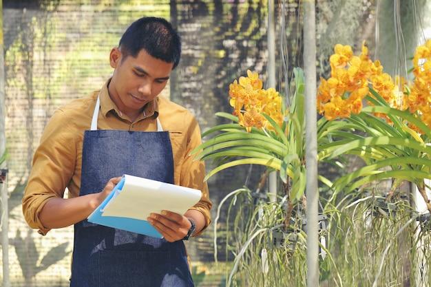 O jovem dono do jardim de orquídeas está verificando a orquídea antes de entregá-la ao cliente. Foto Premium