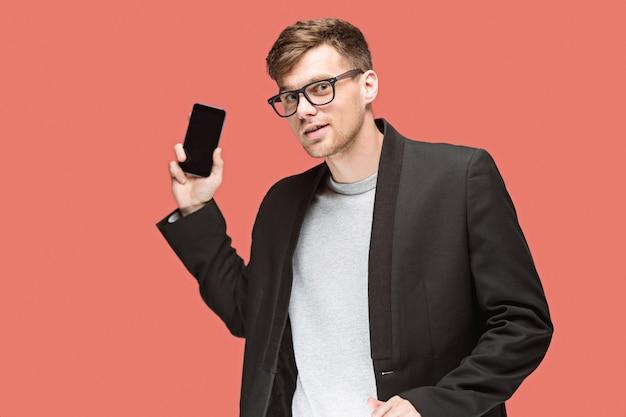 O jovem empresário caucasiano no espaço vermelho, falando no celular Foto gratuita