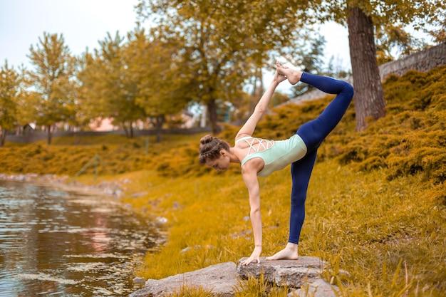 O jovem esbelto jovem iogue executa exercícios de ioga desafiadores grama verde no outono contra a natureza. linda garota desportiva em pé em pose de meia-lua Foto Premium