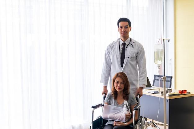 O jovem médico incentivou a paciente do sexo feminino no braço quebrado e na cadeira de rodas. Foto Premium