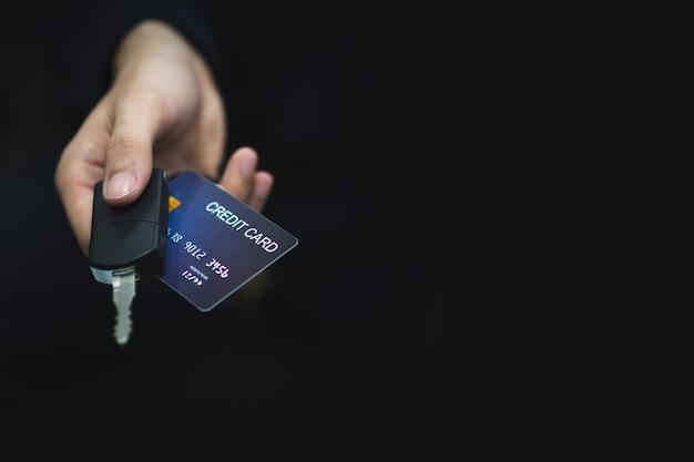 O jovem pagou a dívida do carro pagando com um cartão de crédito com uma chave do carro na mão. Foto Premium