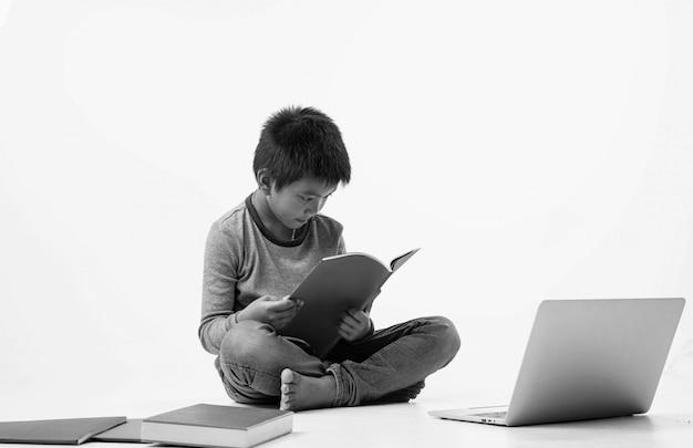 O jovem sentado no térreo, lendo o livro com um sentimento interessado, tom preto e branco Foto Premium