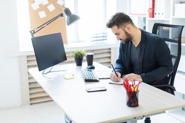O jovem trabalha no escritório em uma mesa de computador com documentos Foto Premium