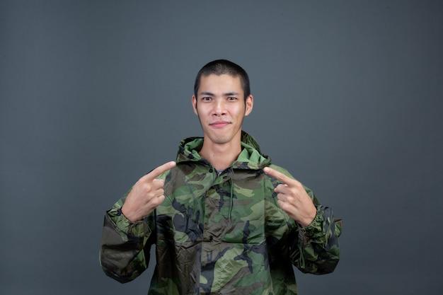 O jovem usa uma capa de chuva de camuflagem e mostra diferentes gestos. Foto gratuita