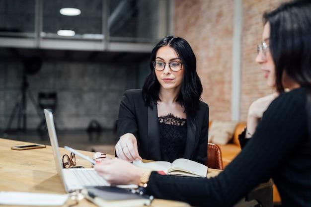 O jovens mulheres interior usando computador portátil Foto Premium