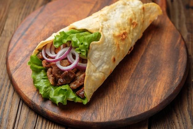 O kebab de doner está encontrando-se na placa de estaca. shawarma com carne, cebola, salada encontra-se em uma mesa de madeira velha escura. Foto Premium