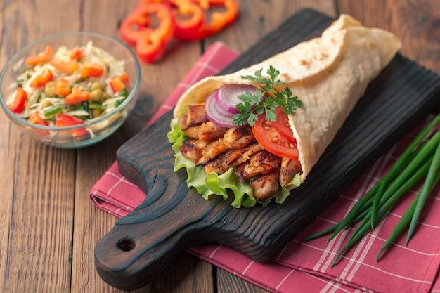 O kebab de doner está encontrando-se na placa de estaca. shawarma com carne de frango, cebola, salada encontra-se em uma mesa de madeira velha escura. Foto Premium