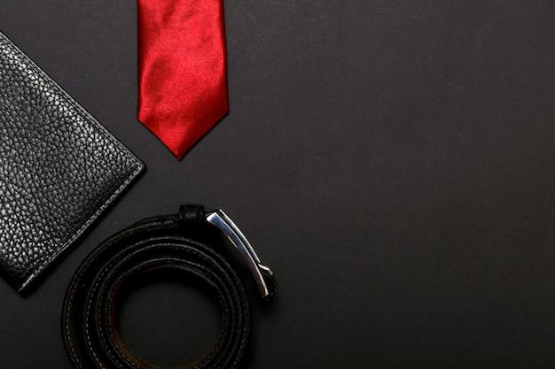 O laço dos homens vermelhos rolados e uma correia de couro no fundo preto, vista superior. Foto Premium