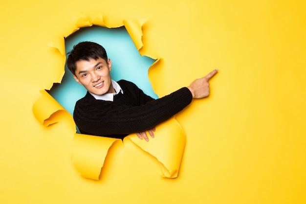 O lado apontado do homem chinês novo com mãos mantém a cabeça no furo da parede amarela rasgada. cabeça masculina em papel rasgado. Foto gratuita