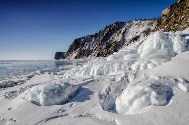 O lago baikal é coberto de gelo e neve, frio forte e gelo azul claro e espesso. pingentes pendurados nas rochas. Foto Premium