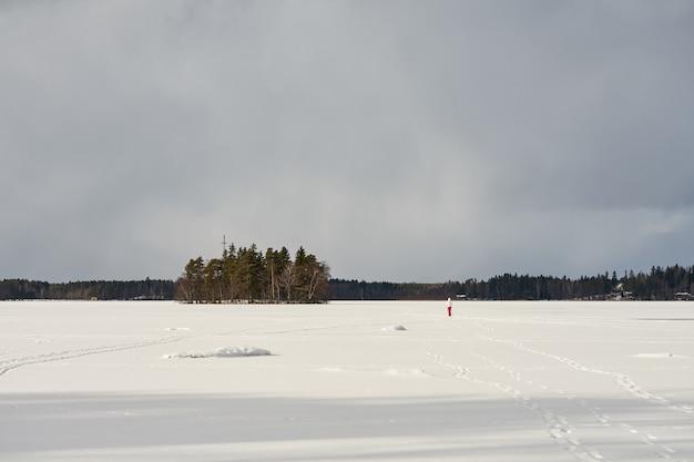 O lago está coberto de gelo e neve em littoinen, finlândia. Foto Premium