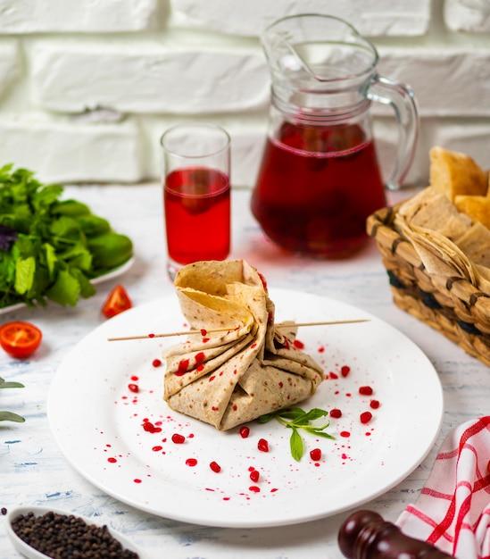 O lanche de lavash rola com as sementes do queijo e do grenate, o pão, os vegetais e o sorvete em uma placa branca. snack Foto gratuita
