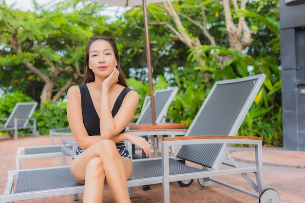 O lazer asiático novo bonito da mulher do retrato relaxa o sorriso em torno da piscina exterior para férias Foto gratuita