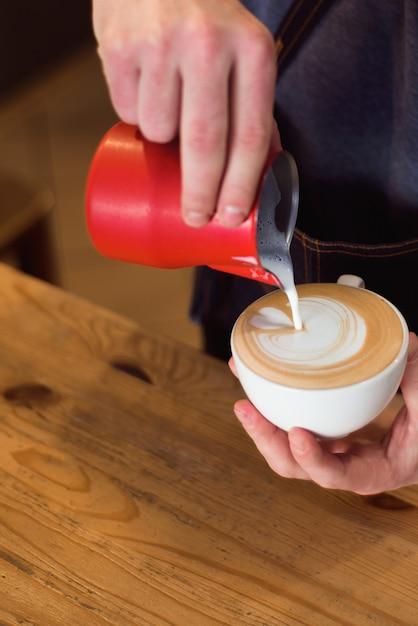 O leite de derramamento de barista no copo de café para faz a arte do latte. Foto Premium