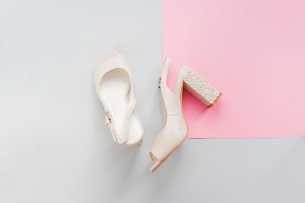 O leite fêmea à moda coloriu as sapatas do salto do casamento isoladas no fundo azul e cor-de-rosa. Foto Premium