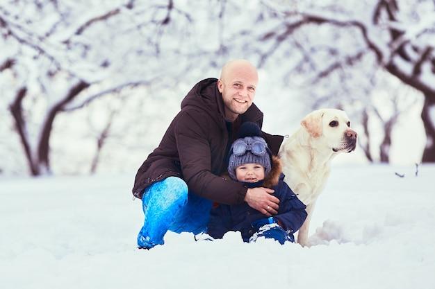 O lindo pai, filho e cachorro sentado na neve Foto gratuita