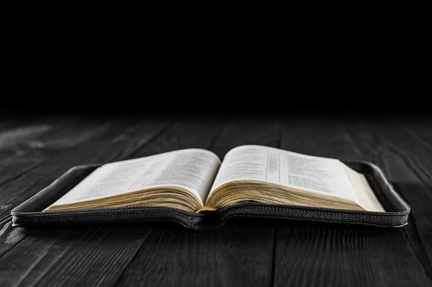 O livro aberto bíblia em madeira preta Foto Premium