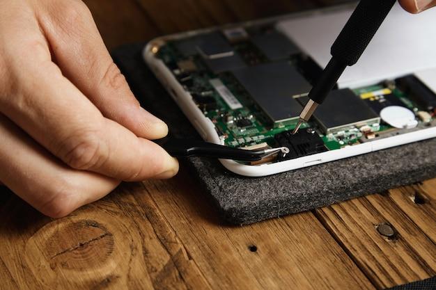 O master usa ferramentas especiais para desmontar o dispositivo eletrônico com cuidado pinças e chave de fenda Foto gratuita