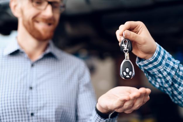 O mecânico dá chaves ao proprietário de carro na garagem. Foto Premium