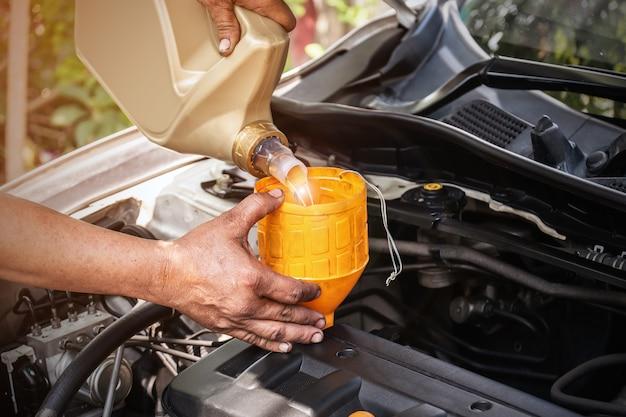 O mecânico de automóveis está adicionando óleo ao motor, indústria automotiva e conceitos de garagem. Foto Premium