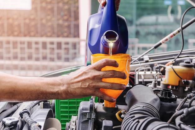 O mecânico de automóveis está adicionando óleo aos conceitos de motor, indústria automotiva e garagem. Foto Premium
