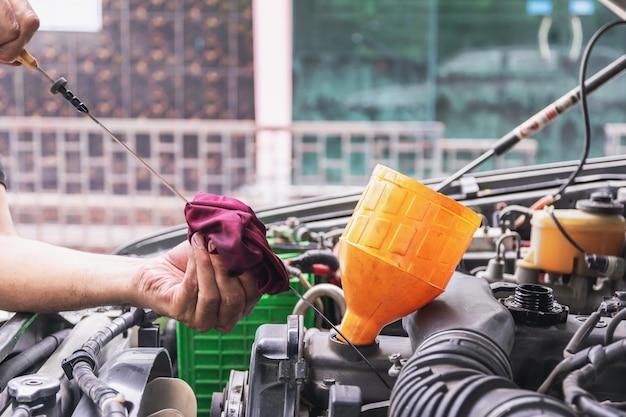 O mecânico de carros está verificando o nível de óleo do motor a partir do medidor de nível de óleo do motor dos conceitos de carro, indústria automotiva e garagem. Foto Premium