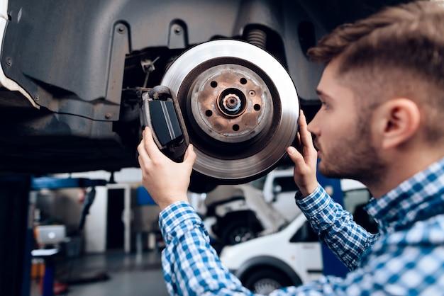 O mecânico novo repara o cubo automotivo na garagem. Foto Premium