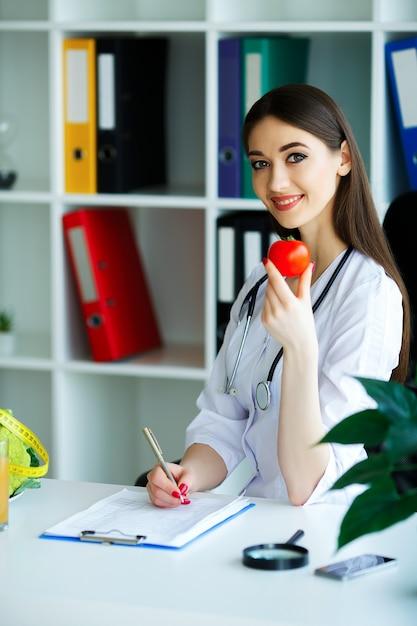O médico assina um plano de dieta. o nutricionista detém os punhados de tomate fresco. frutas e vegetais. Foto Premium