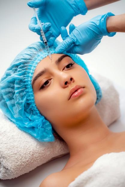O médico cosmetologista faz o procedimento de rejuvenescimento das injeções faciais para apertar e suavizar as rugas na pele do rosto de uma mulher em um salão de beleza. cuidados com a pele cosmetologia Foto Premium