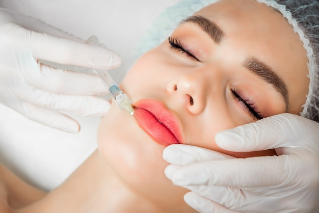O médico cosmetologista faz o procedimento de rejuvenescimento das injeções faciais para apertar e suavizar as rugas na pele do rosto de uma mulher jovem e bonita em um salão de beleza Foto Premium
