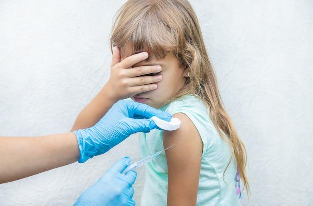 O médico dá à criança uma injeção no braço Foto Premium