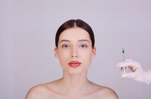 O médico em luvas segura uma seringa perto do rosto da mulher. Foto Premium