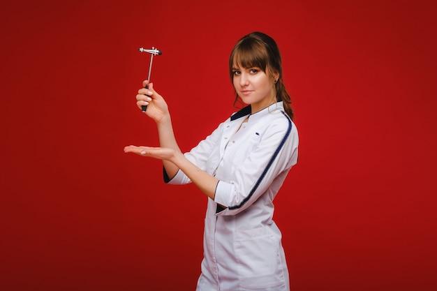 O médico está segurando um martelo neurológico em um fundo vermelho. o neurologista verifica os reflexos do paciente com um martelo. diagnósticos, cuidados de saúde e cuidados médicos. Foto Premium
