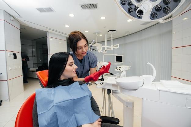O médico mostra um molde da mandíbula do paciente. odontologia Foto Premium