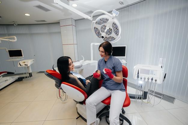 O médico mostra um molde da mandíbula do paciente Foto Premium