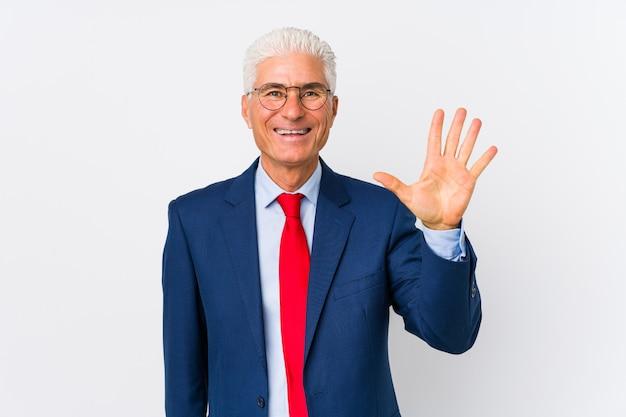 O meio envelheceu o homem de negócio caucasiano isolado sorrindo mostrando alegre número cinco com dedos. Foto Premium