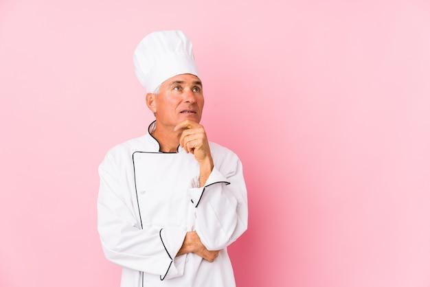 O meio envelheceu o homem do cozinheiro isolado olhando lateralmente com expressão duvidosa e cética. Foto Premium