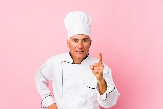 O meio envelheceu o homem do cozinheiro isolado tendo uma ideia, conceito da inspiração. Foto Premium