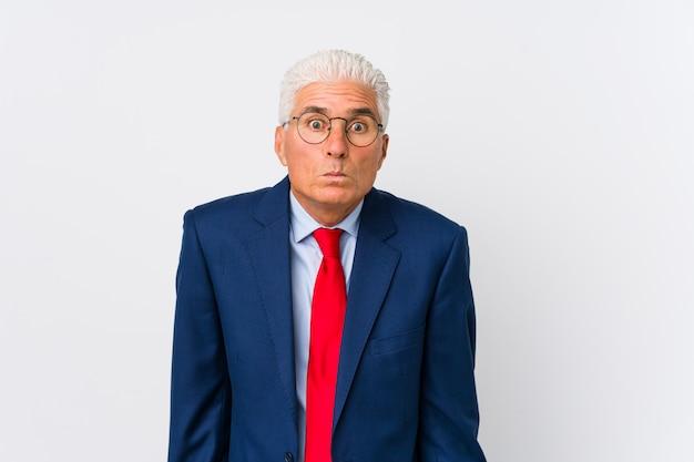 O meio homem de negócios caucasiano envelhecido isolado encolhe os ombros e abre os olhos confusos. Foto Premium