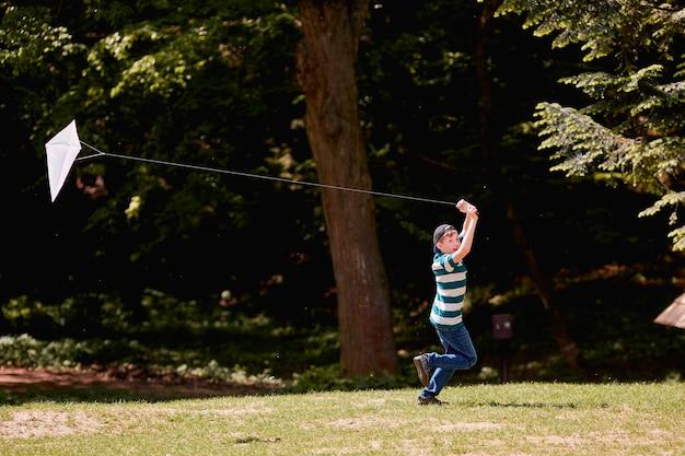O menino andando e brincando com pipa Foto gratuita