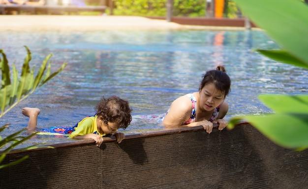 O menino asiático da criança aprende a natação em uma piscina com mamã. - efeito de filtro sunset Foto Premium