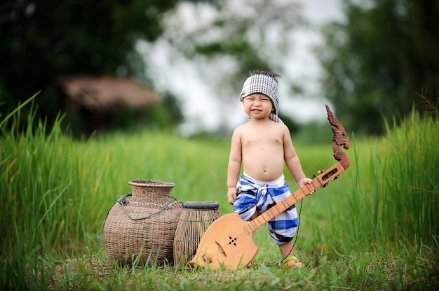 O menino asiático da pesca que sorri na sensação verde do campo do arroz relaxa o ed. Foto Premium