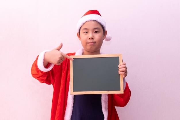 O menino asiático em papai noel veste guardar o tabuleiro vazio. feliz natal Foto Premium