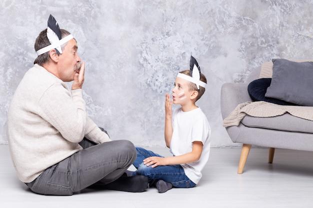 O menino caucasiano e seu avô jogam índios em uma parede de parede cinza. neto e neto sênior jogar na sala de estar Foto Premium