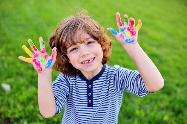 O menino com cabelo encaracolado sem o dente de leite dianteiro mostra as mãos sujas com pinturas e sorrisos multi-coloridas do dedo. Foto Premium