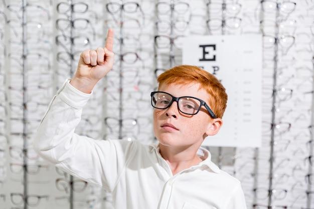 O menino com espetáculo que aponta na direção ascendente que está de encontro aos óculos indica o fundo Foto gratuita